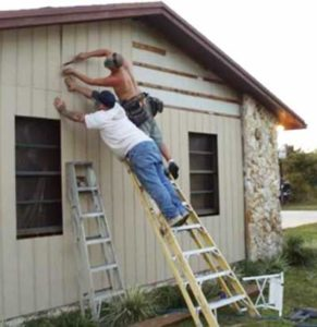 2 men standing on a ladder