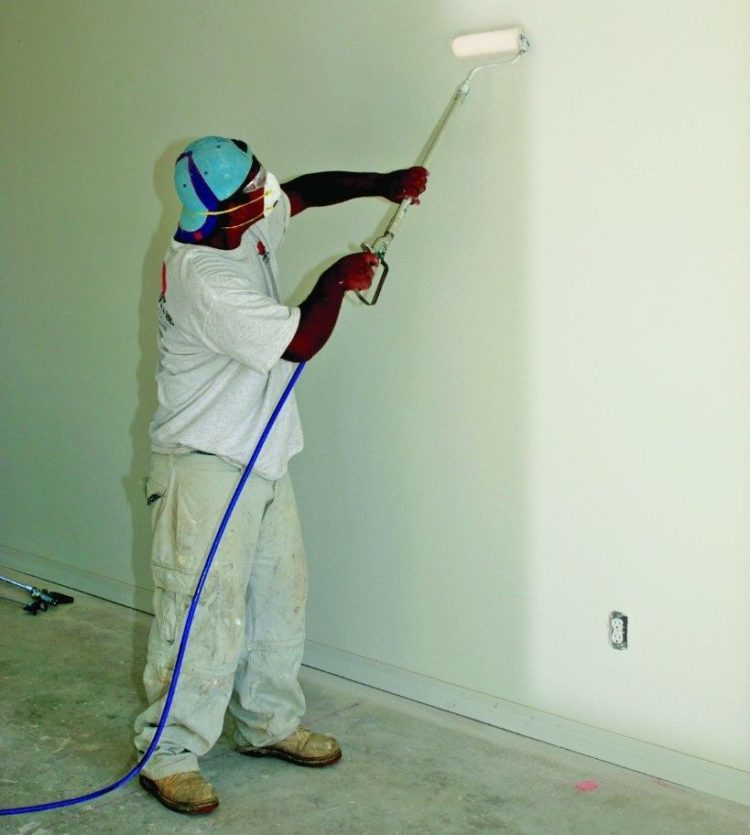worker using a power paint roller