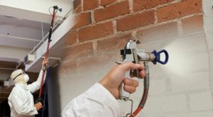 worker using paint sprayer on interior walls