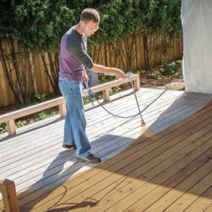 Working man spraying a deck