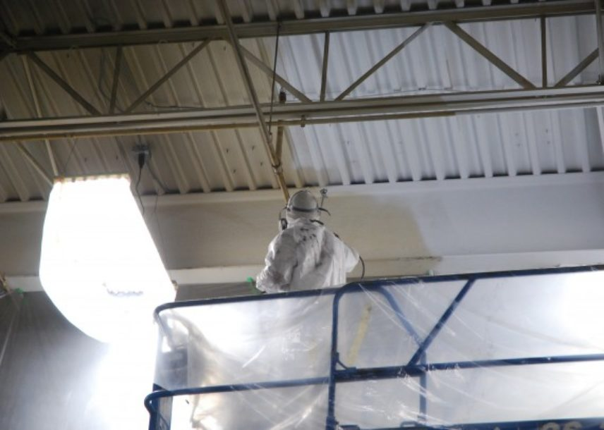 commercial paint sprayer on lift + man wearing suit
