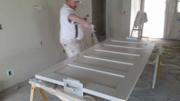 man painting doors with paint sprayer